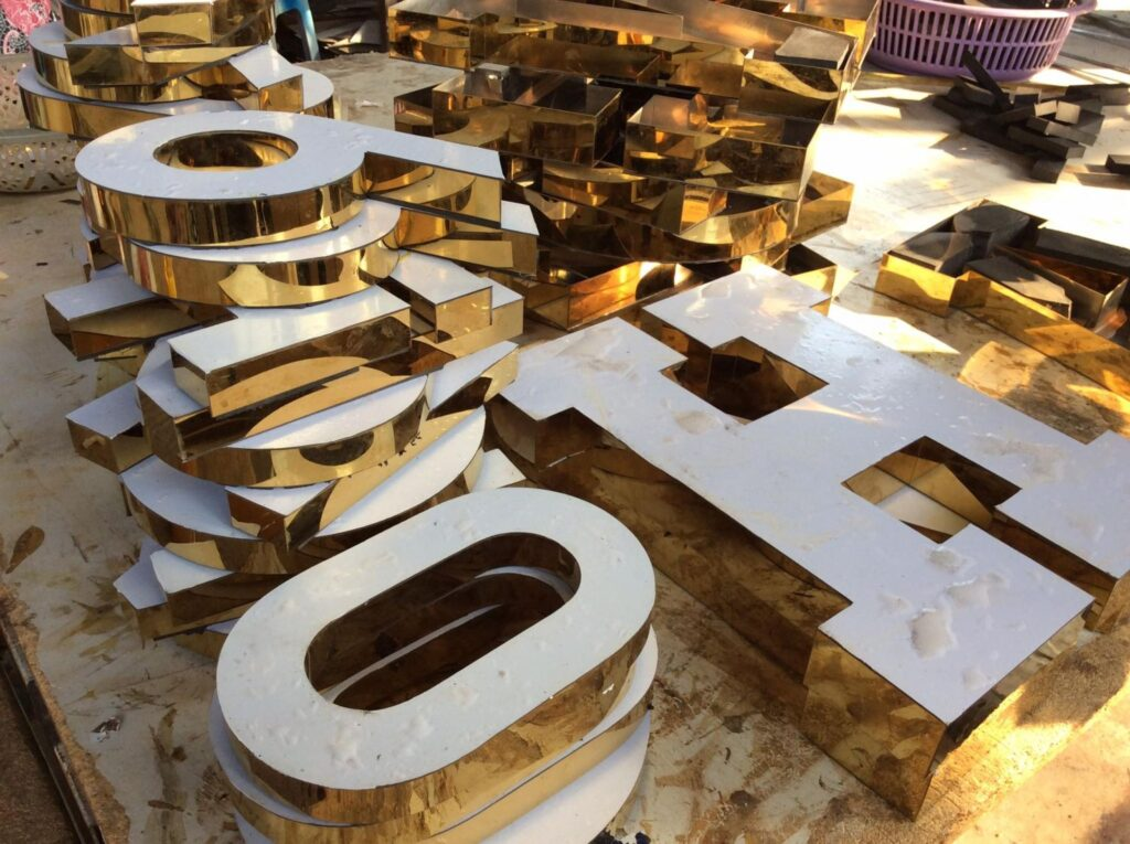 Bảng hiệu chữ nổi Inox vàng xước lộng viền mặt giả đá acrylic màu